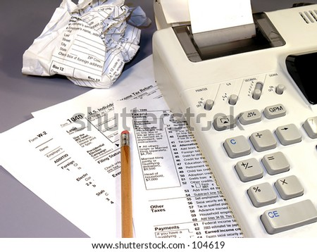 Tax time.  Various IRS forms, calculator, and a pencil.  One of the forms is crumpled. - stock photo
