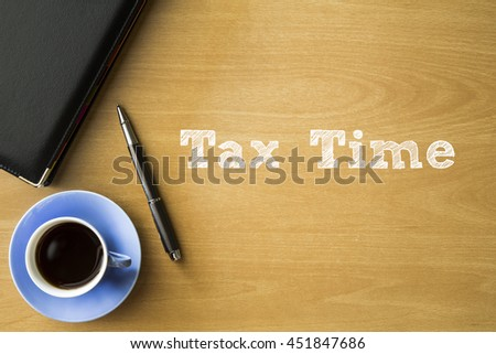 Tax time words writing on wooden desk with notebook, pen and cup of coffee, Business concept. - stock photo