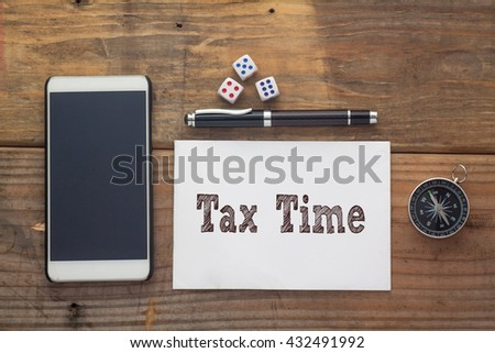Tax Time Words written on white on wooden desk with dice,compass,smart phone and pen.Top view conceptual - stock photo