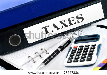 Taxes folder with office tools - stock photo