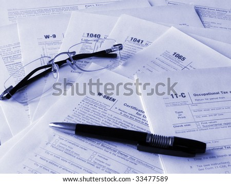 Taxes forms, glasses and pen. Toned blue. Shallow DOF. - stock photo