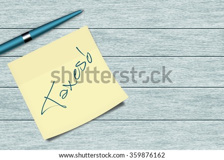 taxes sticky note and pen lying on wooden  desk  - stock photo