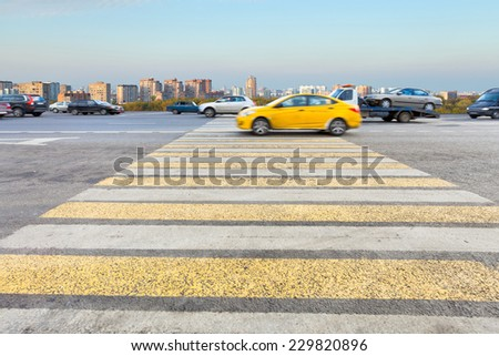taxi at yellow and white crossing zebra of pedestrian crosswalk on urban street - stock photo
