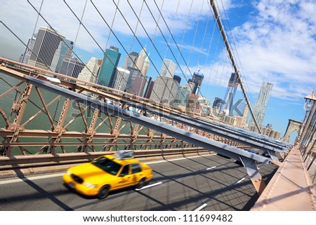 Taxi cab crossing the Brooklyn Bridge in New York, Manhattan skyline in background - stock photo