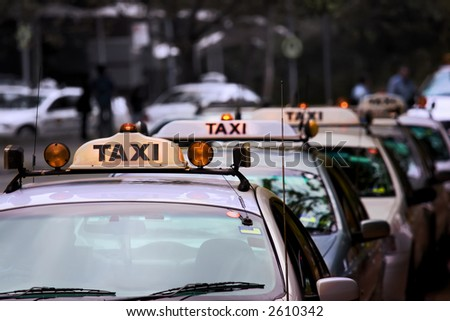 Taxi rank lineup, shallow focus, desaturated background - stock photo
