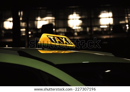 Taxi sign on car roof - stock photo
