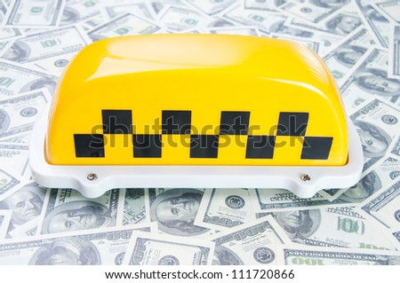 Taxi sign on one hundred dollar bills, studio shot - stock photo