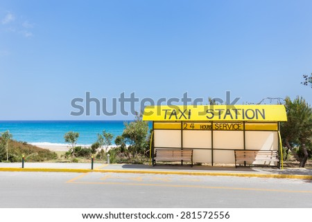 Taxi station along road near blue beach in Greece - stock photo