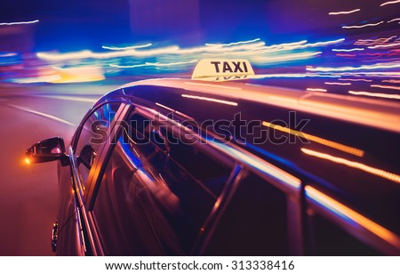 Taxi taking a left turn at night in an urban surrounding, seen from the rear end of the cab - stock photo