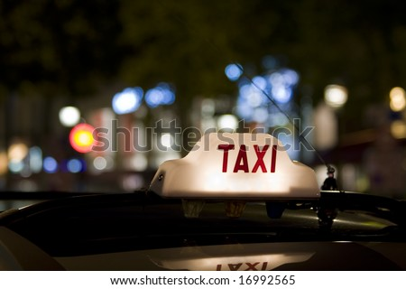 Taxi waiting for a fare in the city with its sign illuminated - stock photo