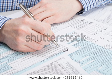 Taxpayer filling out 1040 Tax Form - studio shot
