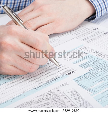 Taxpayer filling out 1040 Tax Form - studio shot - stock photo