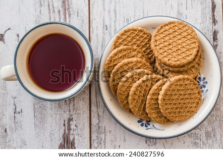 Tea and biscuits in ceramic kitchenware on wooden white background - stock photo