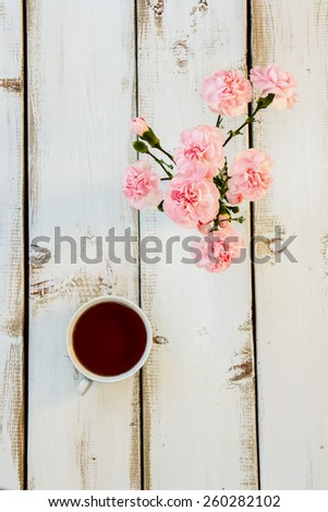 Tea and flowers on white wooden background. Tea ceremony concept. Top view. - stock photo