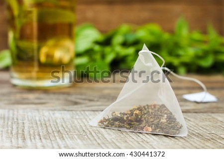 Tea bag on background of mint and and cup of tea - stock photo