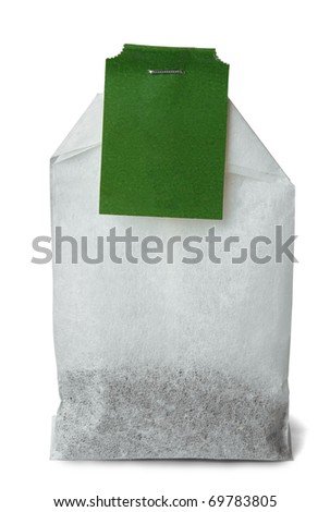 Tea bag with green tag isolated on white - stock photo