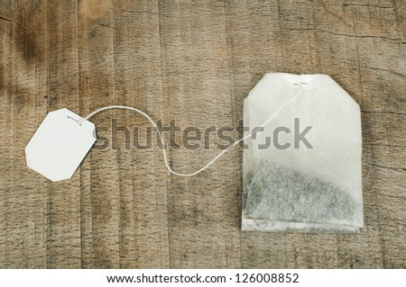 Tea bag with white label on wood plank