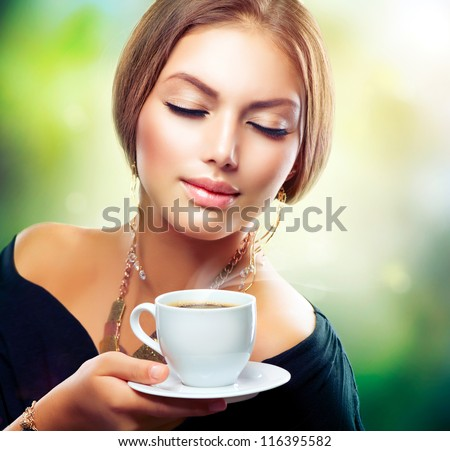 Tea. Beautiful Girl Drinking Tea or Coffee. Healthy Beverage. Woman with Cup over Nature Green Background - stock photo
