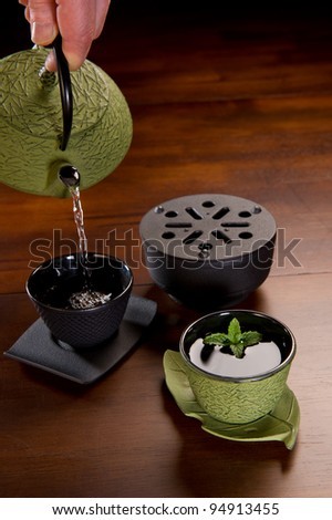 Tea being poured in a traditional Japanese cast iron tea pot and cups. - stock photo