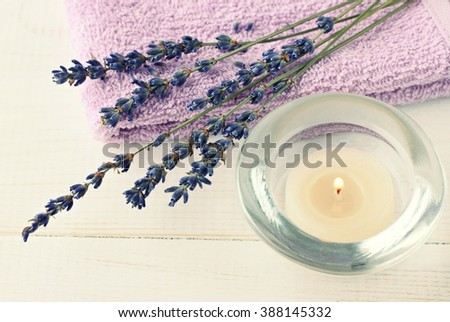 Tea candle and dry lavender herb. Relaxing aromatherapy. Toned. - stock photo