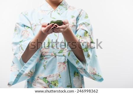 Tea ceremony. Closeup portrait of young beautiful Asian woman in traditional kimono holding out a cup of tea with selective focus while standing against white background  - stock photo