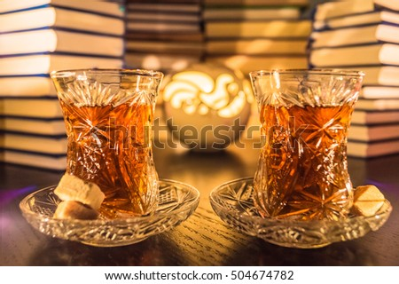Tea ceremony in evening. Two glass of tea on the table, brown sugar, books in the background