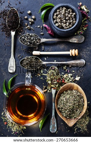 Tea composition with Different kind of tea and old spoons on dark background - stock photo