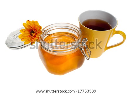 Tea cup and a honey jar, with a flower on it, isolated