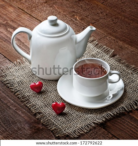 tea cup and  teapot with red hearts on old wooden table   - stock photo