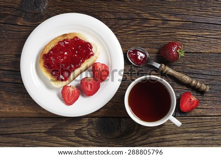 Tea cup and toast with strawberry jam in plate on old wooden table, top view - stock photo
