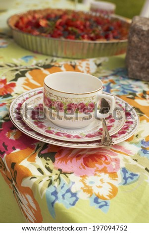 Tea cup on a flowery tablecloth - stock photo