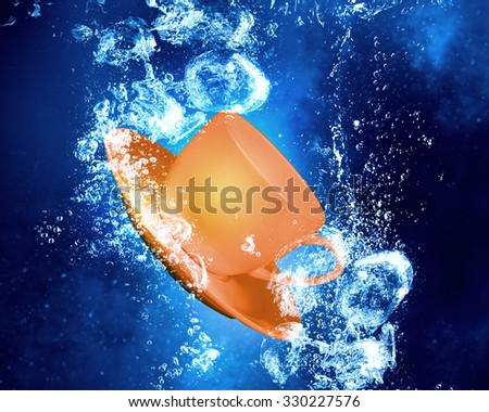 Tea cup sink in clear blue water - stock photo