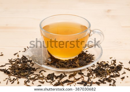 tea cup, tea bag and tea leaves on a wooden table