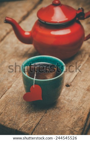 Tea cup with a red heart and a teapot on an old wooden table - stock photo