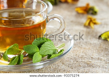 Tea cup with fresh mint leaves, closeup photo - stock photo
