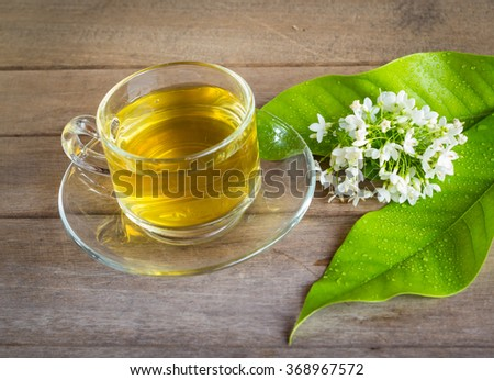 tea cup with green leaves and white flowers  on wood texture