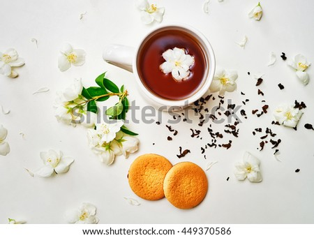 Tea cup with green tea, dried tea leaves and fresh fragrant Jasmine flower and biscuits on white background. Top view composition. - stock photo