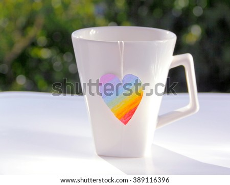 Tea Cup With Rainbow Heart Label. Close up on white tea mug with tea rainbow label heart shape against white table and natural background      - stock photo