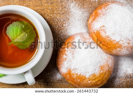 Tea cup with sugar powdered buns on wooden background - stock photo