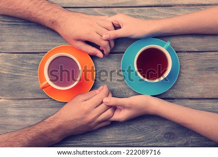 Tea cups and holding hands at the wooden table - stock photo