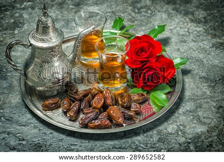 Tea, dates fruits and red rose flowers. Islamic holidays decoration. Ramadan kareem. Oriental hospitality concept. Selective focus. Vintage style toned photo - stock photo