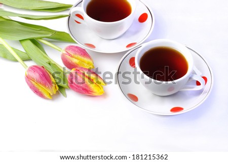 Tea for two. Two cups of tea and tulips