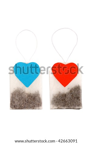 Tea for two. Two tea bags with heart-shaped blue and red labels isolated on white