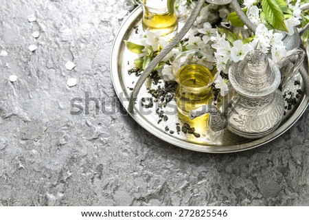 Tea glasses and pot. Oriental silver tableware. Spring flowers decoration. Selective focus - stock photo