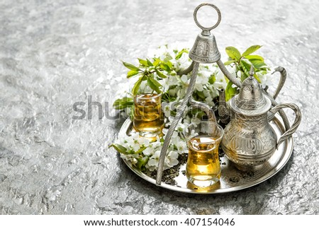 Tea glasses and pot. Silver dishes. Oriental holidays decoration with flowers.  - stock photo