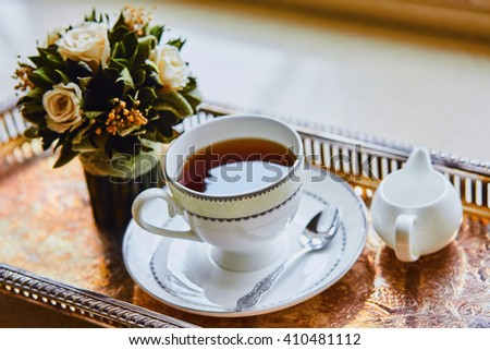 Tea in a beautiful Cup on the metal oriental tray with flowers - stock photo