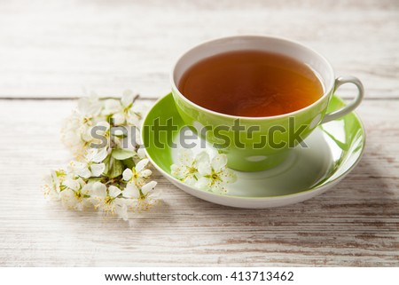tea in a cup and cherry flowers on a table, selective focus
