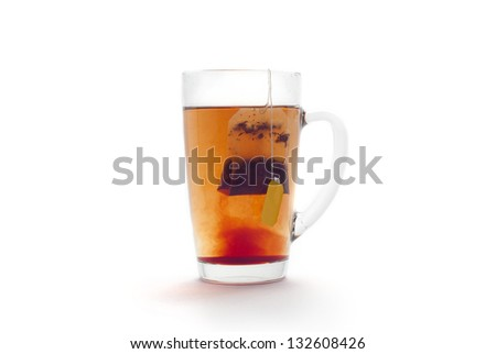 Tea in a glass cup on a white background. Tea bag