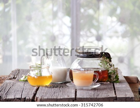 Tea in a transparent cup with honey and milk on a wooden table