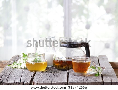 Tea in a transparent teapot submitted with honey and milk